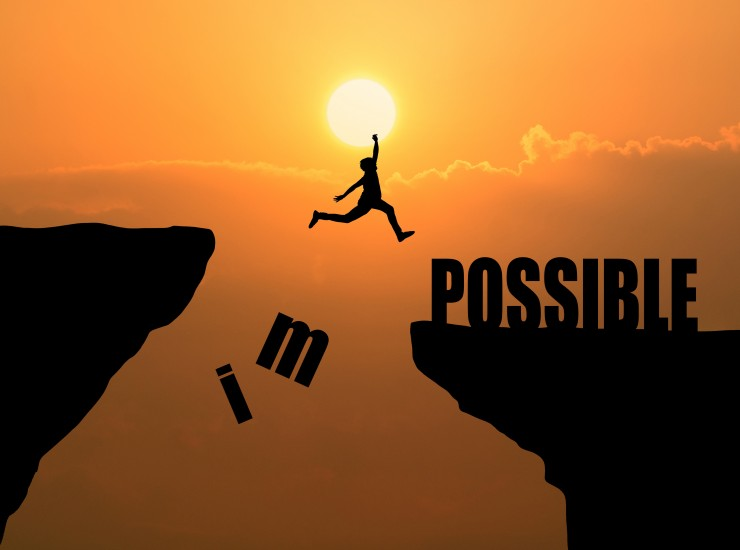 Man jumping over impossible or possible over cliff on sunset background,Business concept idea